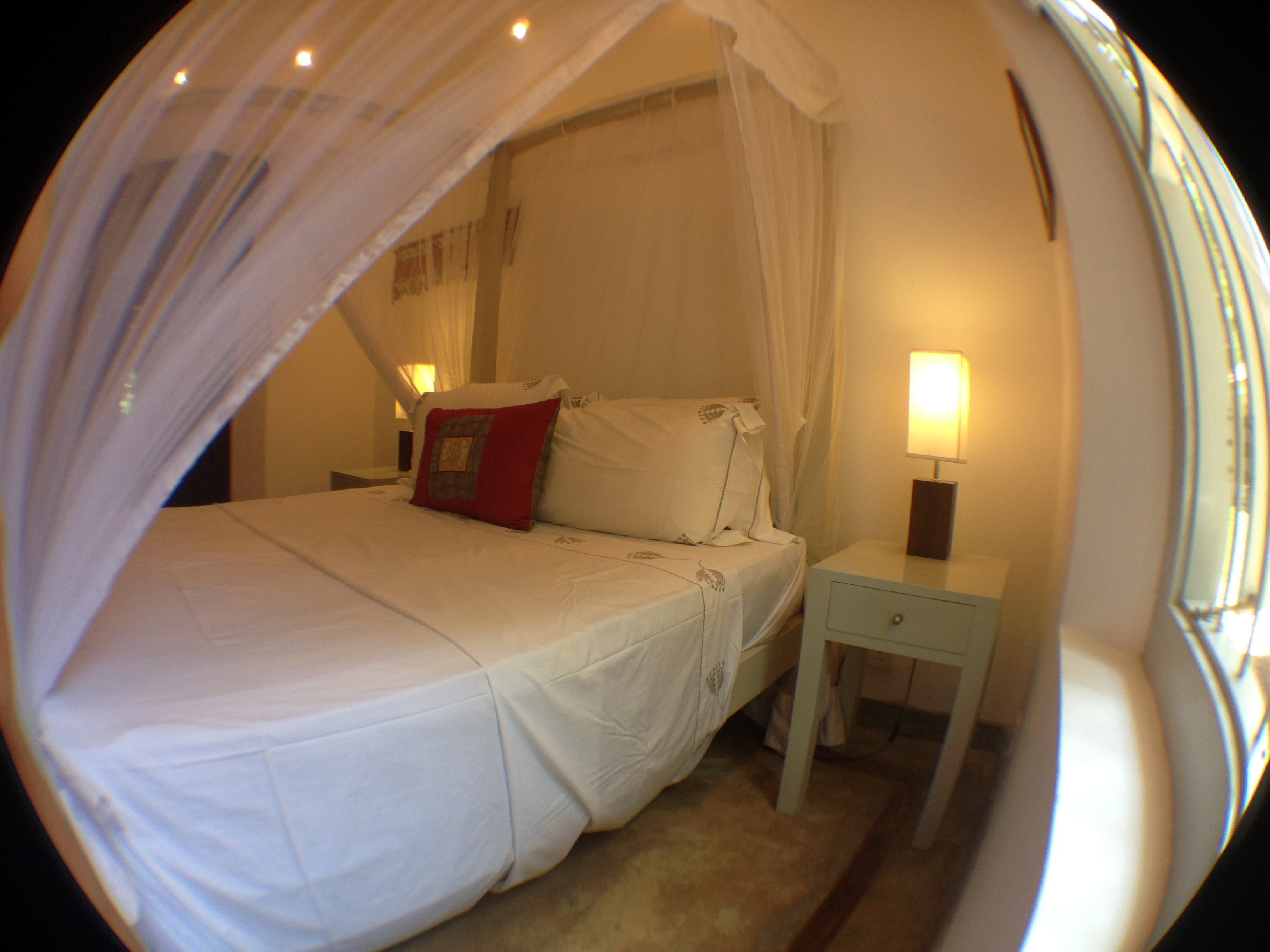 Room features a concrete floor with wooden inlays and a ceiling fan.